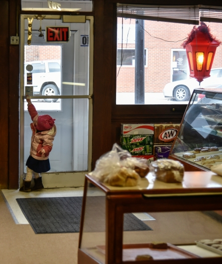 A little girl is ready to go as she tries opening the door while her mom purchases roll on Friday, Jan. 13.