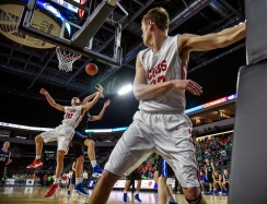 Chamberlain's Rich Marone (33) watches as teammate Riggs Priebe (20) and St. Thomas More's Ryder Kirsch (20) fight for a rebound during a game in the second round of the Class A state tournament on Friday at the Denny Sanford Premier Center in Sioux Falls.