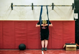 Nash Hutmacher relaxes on bands while his dad Joe Hutmacher does lifts down and back across the gym floor. Joe has gotten back into competitive lifting after a 15 year hiatus largely to work out with his kids. Joe also serves a volunteer strength and conditioning coach for Chamberlain athletics.