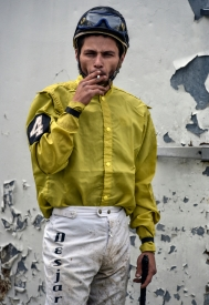 Jockey Cody Desjarlais smokes a cigarette while waiting outside the paddock to before saddling a horse to compete in the Pari-Mutual Horse Races at the Brown County Fairgrounds on Sunday in Aberdeen.