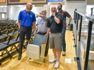 Dakota Wesleyan University basketball coaches Matt Wilber, left, and Jason Christensen, second from right, along with Corn Palace Director Scott Schmidt, right, have a laugh with long time DWU fan Emmanuel 'Junior' Hille as he tells a story from someone sitting in his chair for a basketball game. Hille has been sitting in the same chair, row 5, seat 6, at the Corn Palace since moving to Mitchell in the 70s. Schmidt was replacing the chair and with the help of DWU gave the seat to Hille.