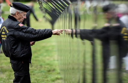 Dennis Anderson, of Watertown, looks for a name on the The Wall That Heals, a Vietnam Veteran Memorial Replica, following the opening ceremonies for the wall on Thursday morning at the rest area in Chamberlain.