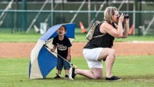 """A young Alexandria fan cries after shouting """"I want to be in the picture"""" and wasn't allowed to be a part of a group picture after the Angels win over the Larchwood Diamonds for the Class B state amateur baseball championship game on Sunday at Cadwell Park."""