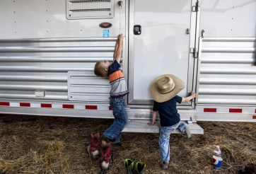 Hazen (4), left, and Paysen (2) Garrett, of Pierre, climb on their mom Amber's trailer while waiting for the start of the Corn Palace Stampede Rodeo on Thursday night at Horseman's Sport Arena in Mitchell. Amber competed in the slack barrel races after the rodeo competition.