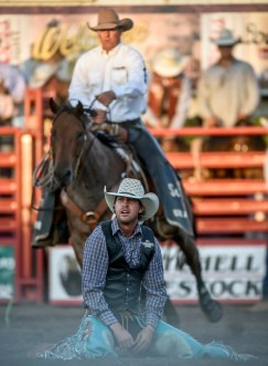 Troy Crowser, of Whitewood, sits on the dirt after being bucked off Uncle Sam in the saddle bronc competition during the final night of the Corn Palace Stampede Rodeo on Sunday night at Horseman's Sport Arena in Mitchell.