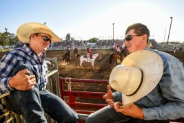 Ross Griffin, left, of Tularosa, New Mexico, and Blaise Freeman, of Snyder, Tex., shoot the breeze while flags and banners are paraded through the arena during the Corn Palace Stampede Rodeo on Thursday night at Horseman's Sport Arena in Mitchell.