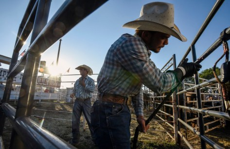 Dustin Muncy, of Polk City, Fla., and Brendon Averett, of New Orleans, La., getting ready in the back of the arena before competing in the bull riding competition on the final night of the Corn Palace Stampede Rodeo on Sunday night at Horseman's Sport Arena in Mitchell.