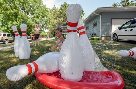 Logan Duerksen (8), left, celebrates as his sister Maci (4) knocks down a bowling pin while taking part in slip-n-slide bowling in their front yard on Monday afternoon in Mitchell.