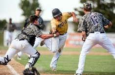 Post 18's Briggs Havlik gets tagged out by Aberdeen Post 24 catcher Drew Geier while Colton Cox (12) backs him up on the play during the first game of doubleheader on Wednesday at Cadwell Park.