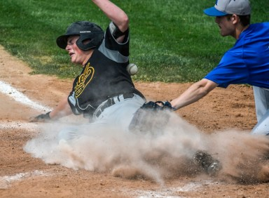 Post 18's Max Schoenfelder slides safely to home scoring on a wild pitch as Renner pitcher Austin Rhode is unable to field the throw from the catch Trey Rogers during the first game of a doubleheader on Saturday at Cadwell Park.