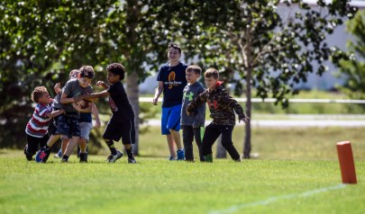 Kids play tackle football while the Dakota Bulldogs take on Buffalo Ridge in the last Southern Plains Football League home game for the Bulldogs at Cadwell Park on Saturday in Mitchell.