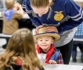 McCook Central senior Natalie Gottlob looks over the head of kindergartener Wyatt Phillips after he made his dirt cup while doing a Food for America project of making treats while teaching kindergarten students about soil as they make their own dirt and worm cups as part of National FFA back in February. (Matt Gade / Republic)