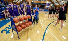 6-year-old Joey Rankin races the ball cart back to the closet as his mom Chelse walks behind him as Kadoka Area and Lyman prepare for the start of their game during the 50th Jones County Invitational Tournament on Thursday in the Harold Thune Auditorium in Murdo.