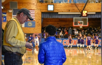 Jim Butt, of Murdo, collects tickets and stamps visitors hands during the 50th Jones County Invitational Tournament on Thursday in the Harold Thune Auditorium in Murdo.